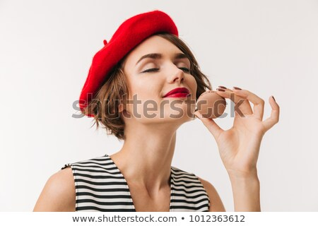 Portrait of a satisfied young woman smelling pastry Stock photo © deandrobot