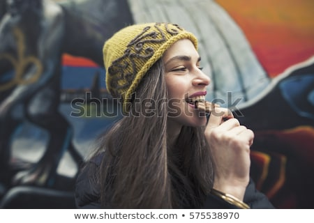Portrait of a happy young woman biting chocolate bar Stock photo © deandrobot