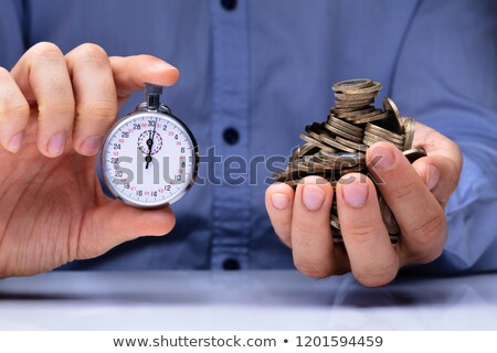 Person Holding Stopwatch And Golden Coins Stock photo © AndreyPopov