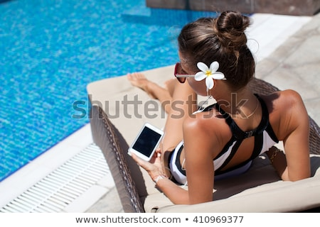 Happy smartphone woman relaxing near swimming pool listening with earbuds to streaming music. Beauti Stock photo © galitskaya