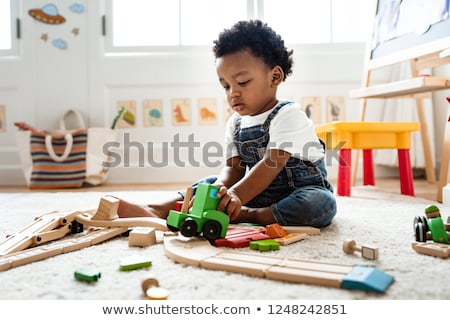 Children play with wooden toy, build toy railroad at home or daycare. Toddler boy play with crane, t Stock photo © galitskaya