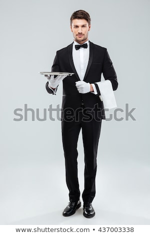 Happy young waiter in tuxedo holding serving tray Stock photo © deandrobot