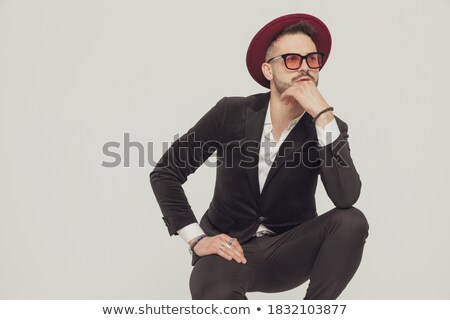 guy with sunglasses sitting and thinking with hand on chin Stock photo © feedough