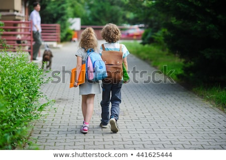 Stock photo: Two boys of primary with school bags behind the back.