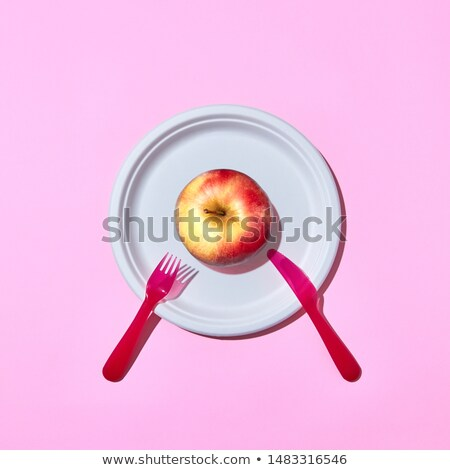 Fresh apple on a plate served with plastic knife and fork Stock photo © artjazz