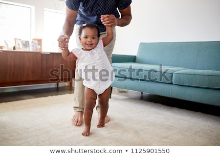 Stock photo: father helping baby daughter with walking at home