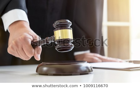 close up of male lawyer or judge hands striking the gavel on so stock photo © freedomz