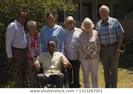Front view of happy senior friends standing with one disabled looking at camera on sunny day in gard Stock photo © wavebreak_media