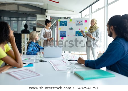 Front view of mixed race male and female executives discussing business over laptop in modern office Stock photo © wavebreak_media