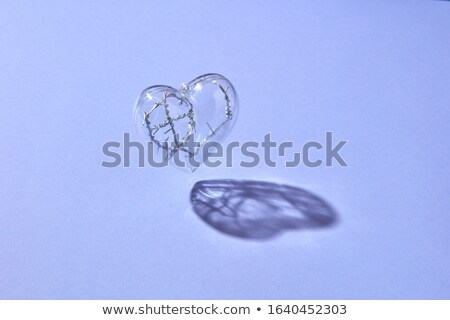 Floating clear heart with twisted wire inside. Stock photo © artjazz