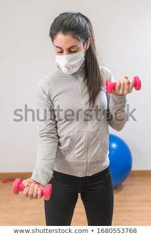 Beautiful woman staying fit during quarantine doing fitness exercise at home Stock photo © Kzenon