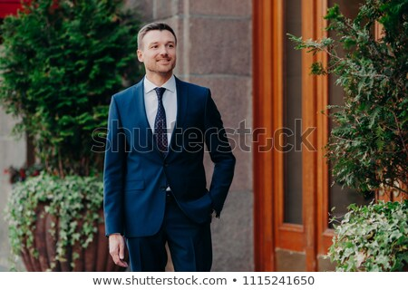 Outdoor view of satisfied young male banker in formal clothing, stands near some building, keeps han Stock photo © vkstudio
