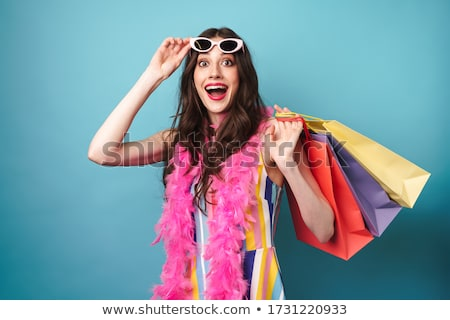 Image of surprised woman in boa holding sunglasses and shopping bags Stock photo © deandrobot