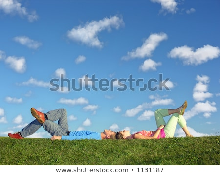 Stock photo: couple lies on meadow with cloud