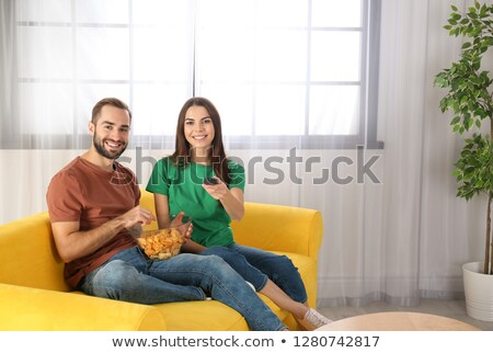 Portrait of a caucasian couple relaxing on the sofa and eating pop-corn in the living-room  Stock photo © wavebreak_media