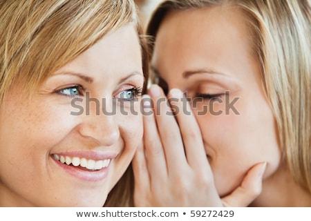 cute woman telling her friend a secret in a living room stock photo © wavebreak_media