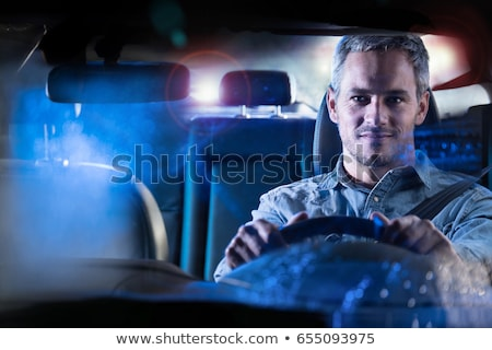 young man driving his modern car at night stock photo © lightpoet