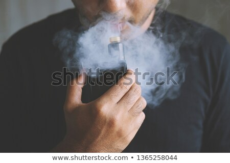 young man holding a cigarette in his hand stock photo © feedough