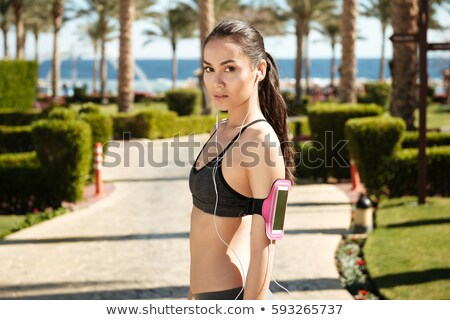 Charming young sportswoman with armband and earphones listening to music Stock photo © deandrobot