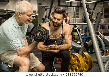 Stock photo: senior male at gym with instructor