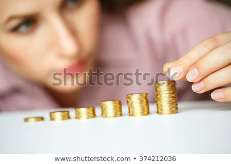 Woman stacking gold coins into increasing columns Stock photo © vlad_star