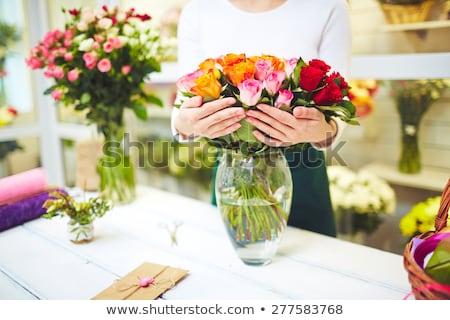 Női virágárus tart váza friss rózsaszín Stock fotó © artjazz