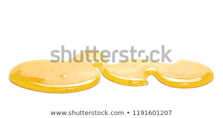 Dripping sweet honey into a puddle of fresh organic syrup on a gray background. Pure natural sweet g Stock photo © artjazz
