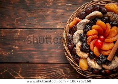 Mix of dried fruits in a small wicker basket on wooden table Stock photo © dash