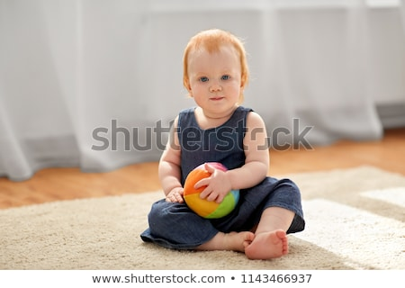 lovely redhead baby girl with toy ball at home stock photo © dolgachov