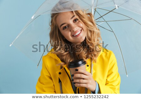 photo of content woman 20s wearing yellow raincoat standing unde stock photo © deandrobot
