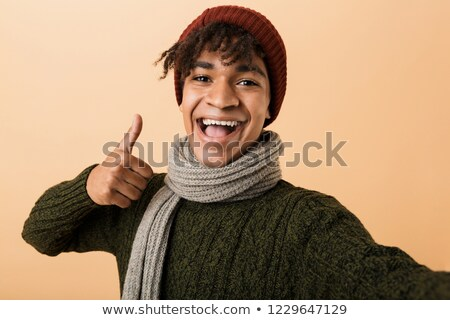 Portrait of happy teen man wearing hat and scarf gesturing at ca Stock photo © deandrobot
