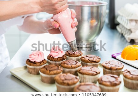 Women in pastry bakery glazing cupcakes Stock photo © Kzenon