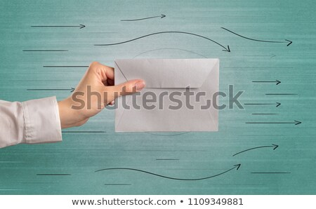 Hand holding envelope with arrows around Stock photo © ra2studio