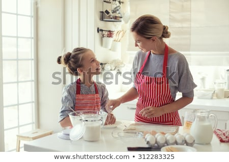 mother and daughter making dough at home kitchen Stock photo © dolgachov