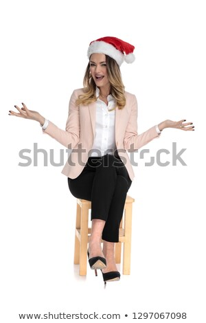 santa businesswoman sits and makes inviting gesture Stock photo © feedough