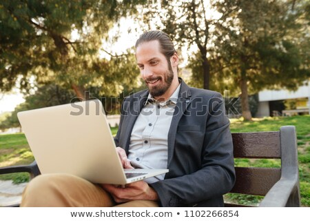 Picture of businesslike handsome man with tied hair working on s Stock photo © deandrobot