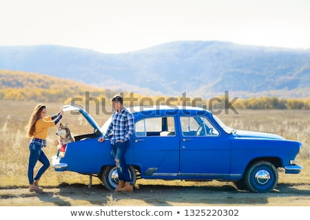 Stock photo: Portrait of a young family with a dog near a convertible.