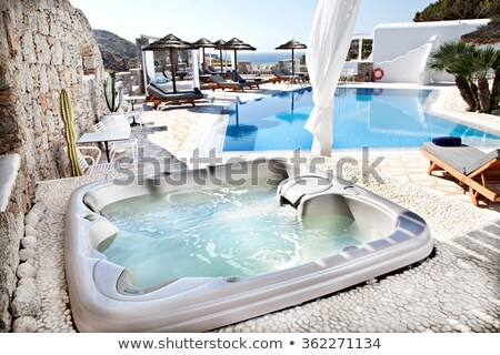 Spa resort couple relaxing enjoying jacuzzi hot tub swimming pool outdoors on summer vacation travel Stock photo © Maridav