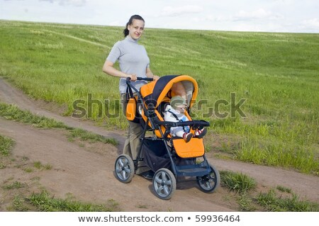 Stockfoto: Mother Takes Baby In A Stroller On The Way