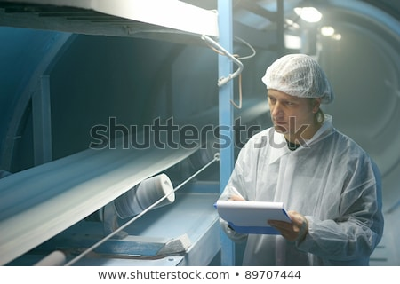 Young production control engineer in workwear and protective headphones Stock photo © pressmaster