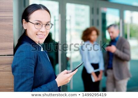 элегантный деловая женщина смартфон Постоянный углу офисное здание Сток-фото © pressmaster