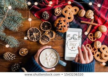 Girl having drink and scrolling in smartphone while going to enter online shop Stock photo © pressmaster