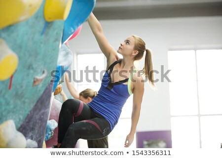 Fit blonde woman with ponytail holding by one of small rocks on climbing wall Stock photo © pressmaster