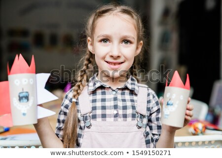 Cute smiling schoolgirl showing scary halloween toys made up of rolled paper Stock photo © pressmaster