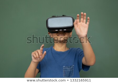 Front view of playful Asian schoolboy using virtual reality headset against greenboard in a classroo Stock photo © wavebreak_media