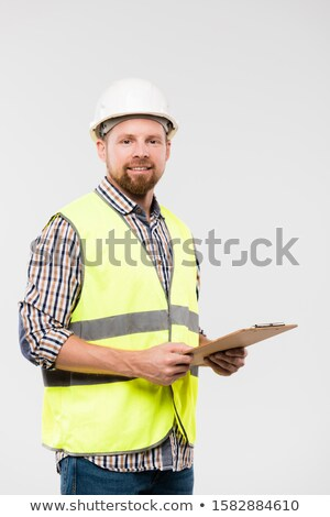 Cheerful engineer with clipboard looking at you while standing in isolation Stock photo © pressmaster