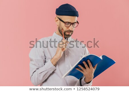 Concentrated unshaven adult man holds blue textbook and pencil, reads necessary information, has ser Stock photo © vkstudio