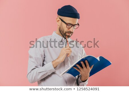 Photo of handsome male author has dark bristle, holds pencil and book, underlines necessary informat Stock photo © vkstudio