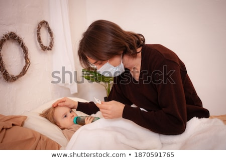 Sick man in bed bed with medical face mask, taking medicines. Stock photo © Margolana