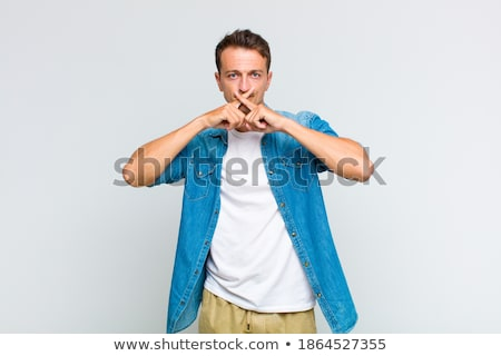Portrait of displeased young man gesturing silence sign Stock photo © deandrobot